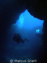 A diver going through Cirkewwa Arch on Malta's north west... by Marcus Grant 